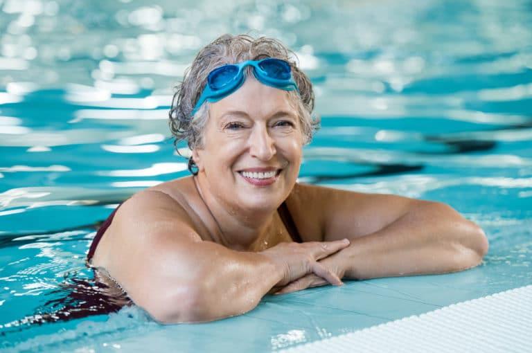 Eine ältere Dame beim Schwimmen im Hallenbad