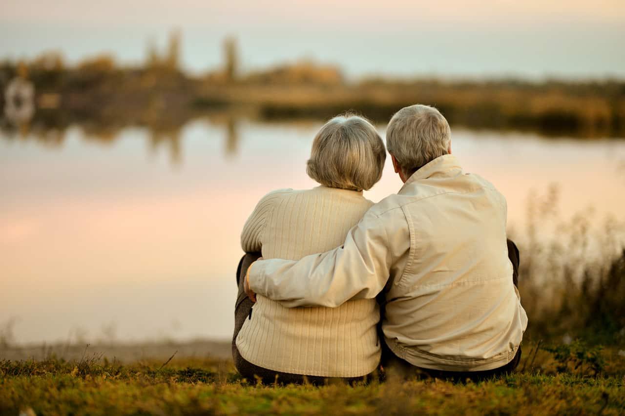 Ein älteres Paar sitzt an einem See