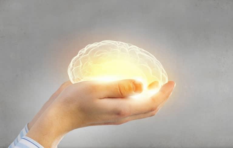 Jemand hält ein leuchtendes Gehirn in den Händen. Es ist ein Symbol für die Gesundheit des Gehirns und mögliche Demenzformen