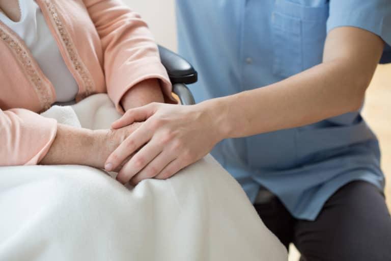Eine Altenpflegerin hält die Hand einer alten Frau