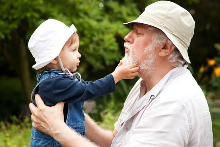 Ein alter Mann mit einem kleinen Kind im Arm