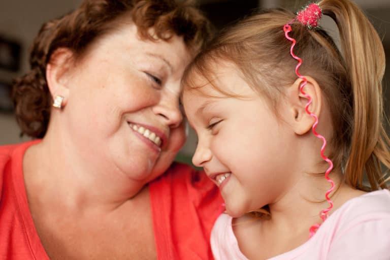 Wie kann man Demenz vorbeugen? Eine ältere Frau ist mit einem Kind zu sehen, beide sind glücklich