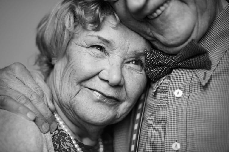Ein älteres Paar, er hält sie, sie lieben sich.