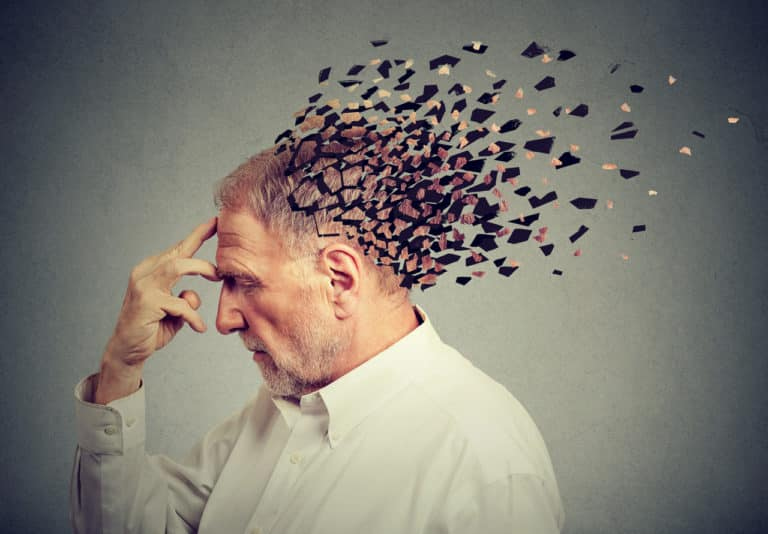 Ein älterer Mann hält sich die Hand an die Stirn, sein Kopf löst sich auf als Symbol für Alzheimer Demenz