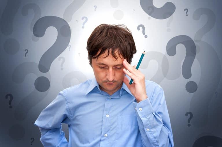 Ein Mann mit blauem Hemd versucht sich zu erinnern, es sind Fragezeichen im Hintergrund als Symbol für Vergesslichkeit