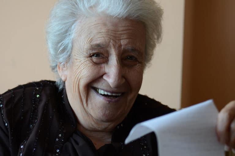 Eine alte lachende Dame mit einem Zettel