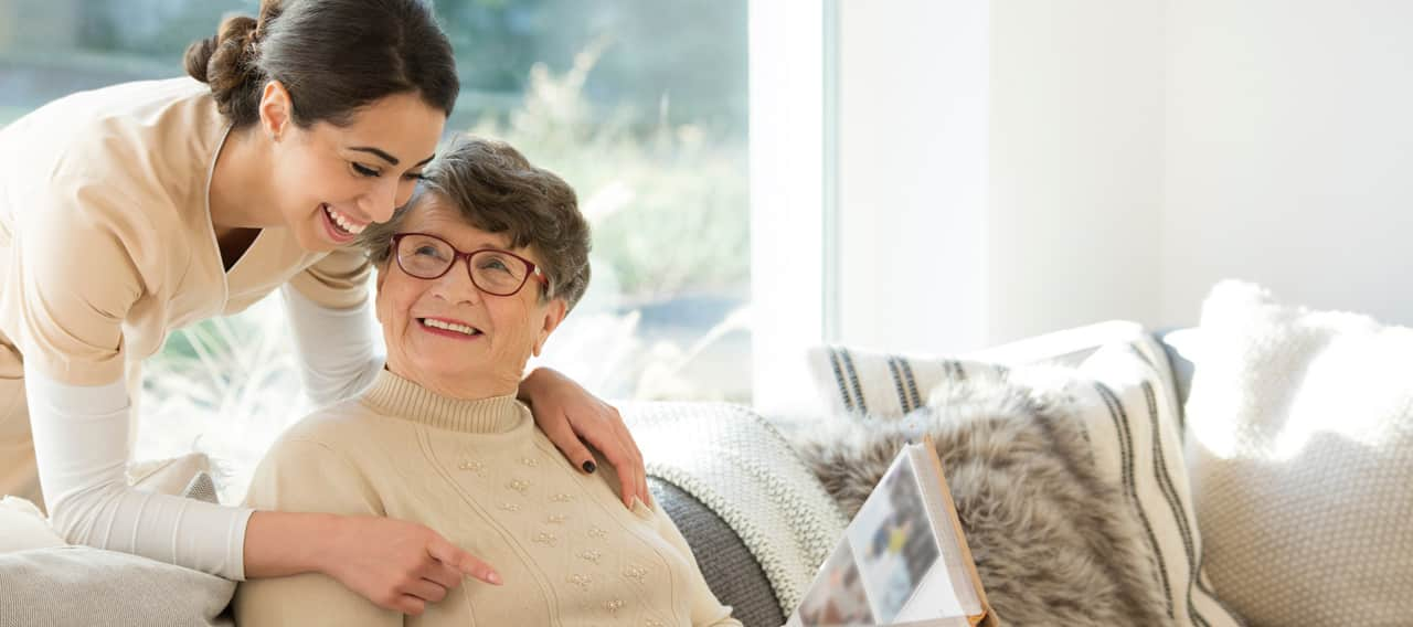 Eine freundliche Betreuerin und eine ältere Frau
