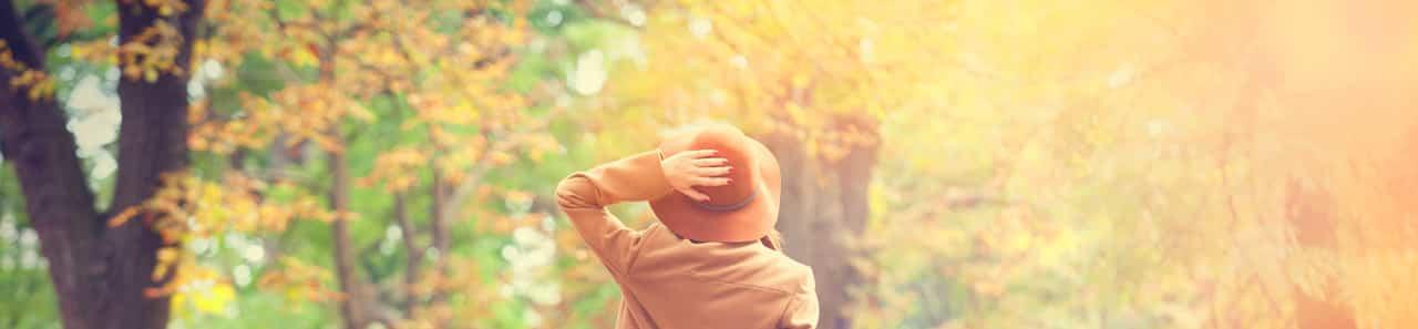 Eine Frau steht in der Sonne und hält sich den Hut