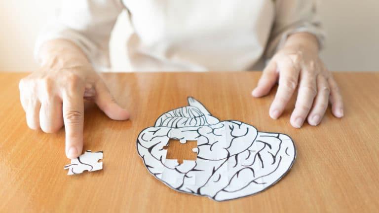Eine ältere Frau sitzt vor einem Papierbild eines Gehirns und entfernt ein Puzzlestück